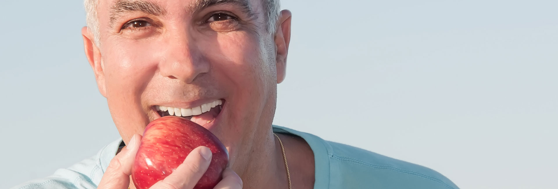 Elderly man with strong teeth eating an apple